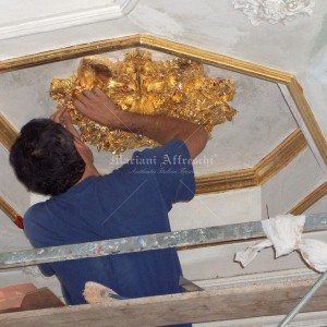 Gold leaf decoration of coffered ceiling with stuccoes. Private villa in Italy